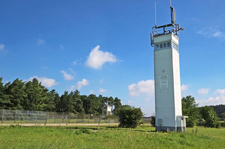 DDR-Grenzturm mit dem Eingang rechts in Richtung Thüringen orientiert. Im Bildhintergrund der ehemalige US-Kontrollturm.