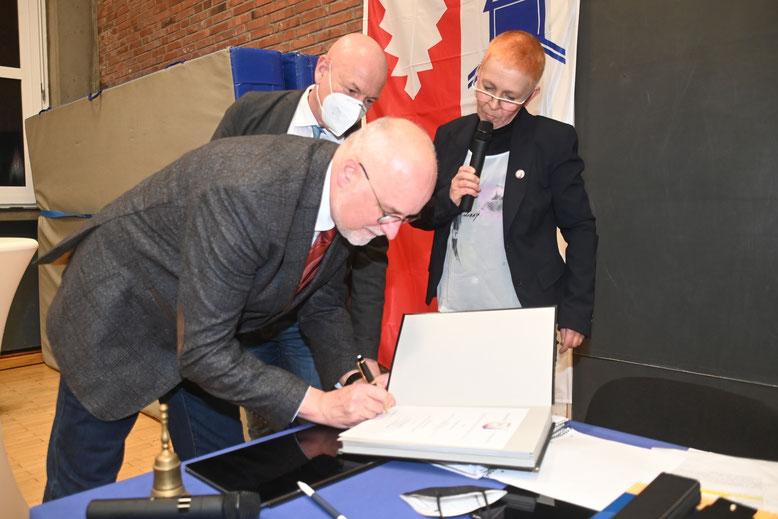 Im Beisein von Amtsdirektor Andreas Faust und Dunja Pucks unterschreibt Johann Hansen die Ernennungsurkunde.