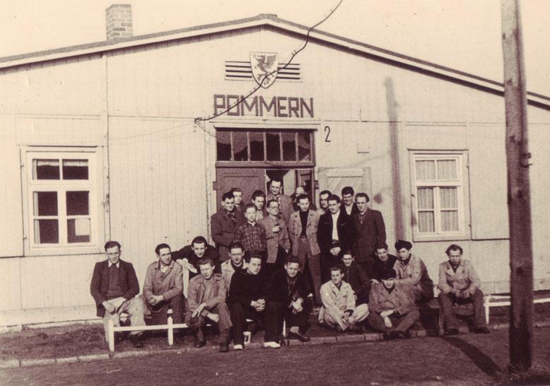 """Jugendliche vor ihrer Unterkunftsbaracke """"Pommern"""". Die Baracken wurden im Notaufnahmelager nach den verlorenen Ostdeutschen Provinzen benannt. Foto: Erika Glenewinkel, Februar 1953"""