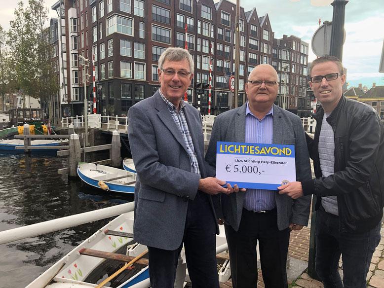 Voorzitter van Lions Club Alkmaar, Ian van Adelberg (rechts), overhandigt de cheque met de opbrengst van 2019 aan Stichting Help-Elkander: voorzitter Johan Borchelt (midden) en penningmeester Richard den Bak (links) [foto: Martijn Wokke]