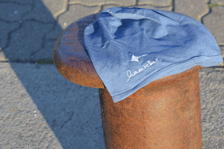 honourebel Slow Fashion. Hochwertige, leichte Sommermütze. Beanie mit gesticktem Logo Schriftzug mit Rochen aus 100 % Biobaumwolle bei Sonnenuntergang am Segelhafenhafen. Blau meliert und hellblau, Ton in Ton.