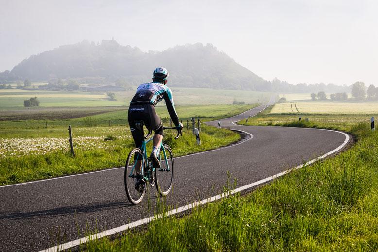 Rennradfahrer in Wiesenlandschaft