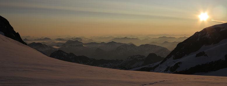 Morgenstimmung vor der Marco e Rosa Hütte. Unter der Sonne die Fortezzafelsen des Palü. Unmittelbar links davon die Gipfel des Val da Camp