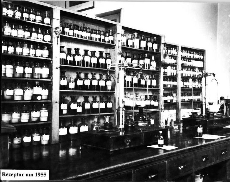 alter Rezeptur der Berg Apotheke um 1955, Vordergrund Arbeitsfläche aus Holz mit zwei Feinwaagen im Hintergrund Aufbewahrungsgefäße für Chemikalien und Rezepturmaterial Braunglasflaschen