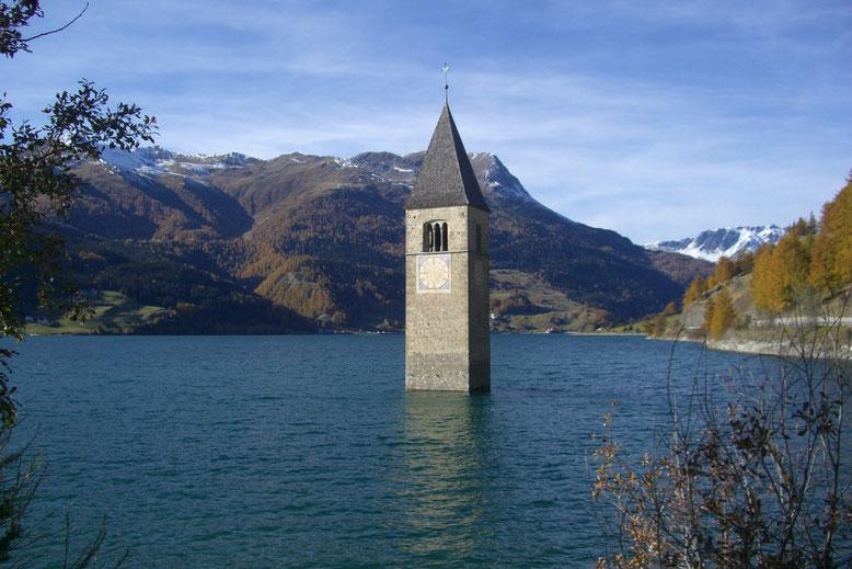 Denkmal und Wahrzeichen von Südtirol und den Vinschgau: Der Turm im Reschensee in Reschen. Blick Richtung Piz Lad und Reschenpass