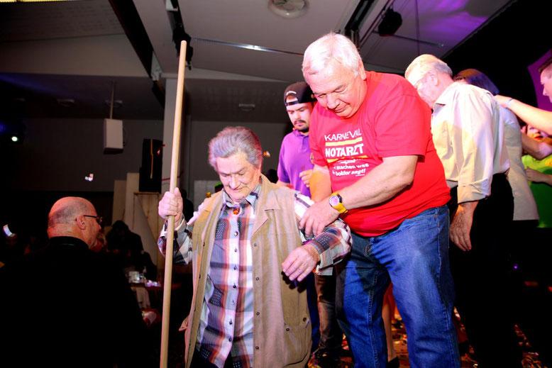 Fritz Linko, ganz Kavalier, hilft WC-Frau Hilde Mößlacher von der Bühne