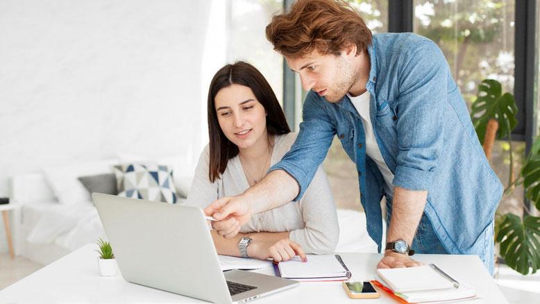 Zwei Personen lernen an einem Laptop. Nachhilfe durch einen Nachhilfelehrer.