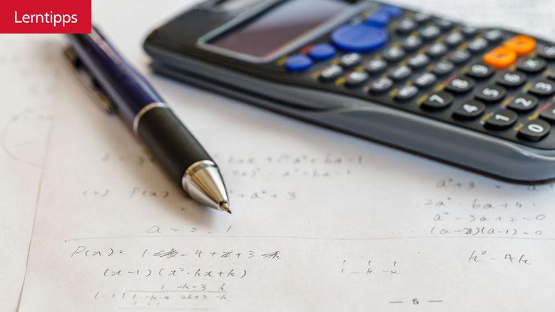 Mathe Formeln mit Taschenrechner und Bleistift.