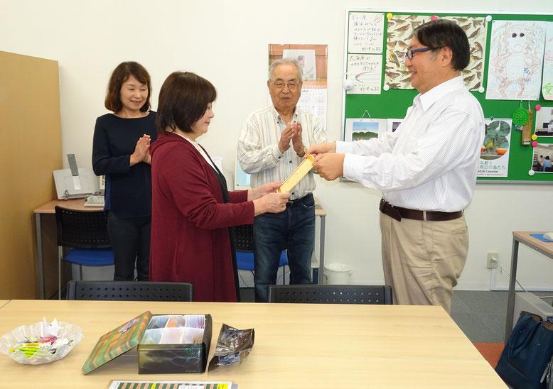 他の生徒さんに祝福されて、先生から修了証を授与される生徒さん