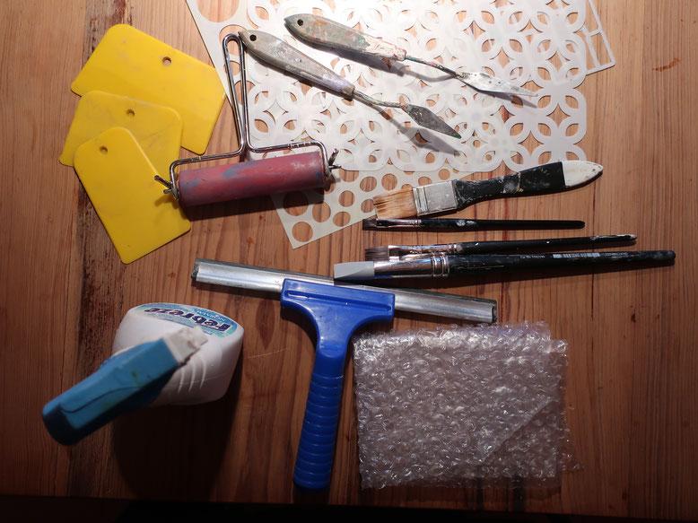 Malmesser, Rakel, Duschabzieher, Luftpolsterfolie, Sprühflasche mit Wasser, ggf. Schablonen, ggf. Rolle