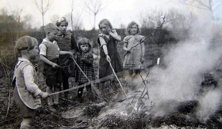 Herbstliche Feuer gab es auch. Kinder zieht es magisch an wenn es im Garten knistert und jeder möchte sein Stöckchen ins Feuer halten.....damals wie heute.