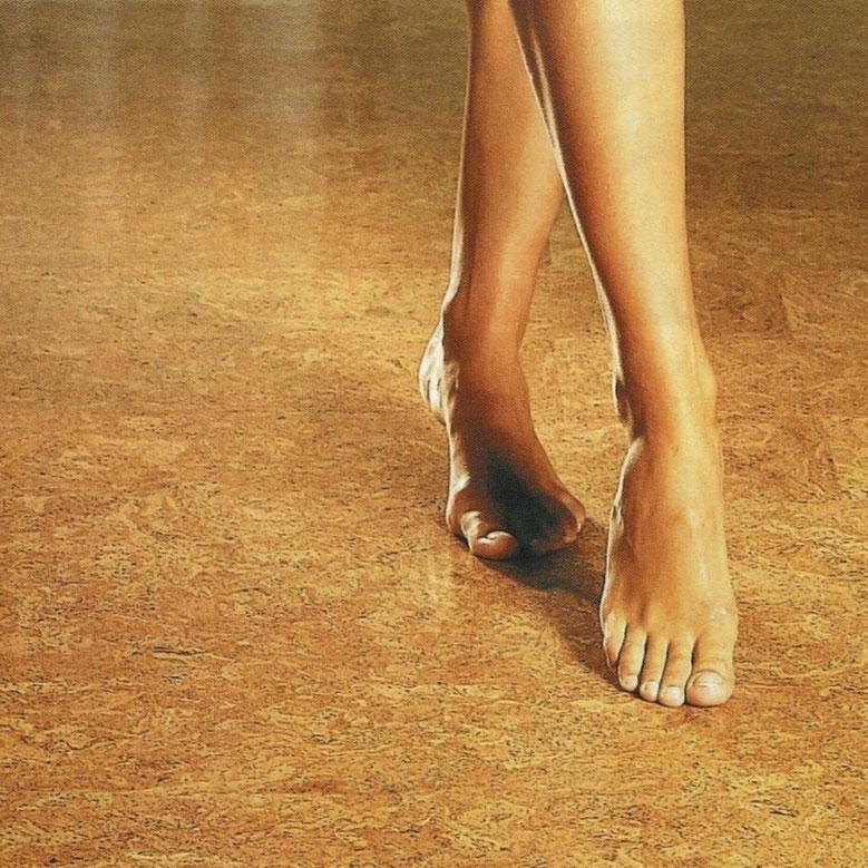 Frauenbeine gehen barfuß über Korkboden.
