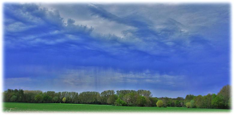 Das Farbenschauspiel: Grüne Erde, blaugraue Wolken & fernes Abregnen