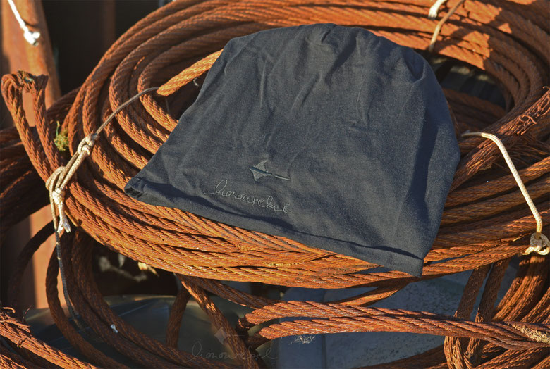 honourebel Slow Fashion. Leichte Sommer Mütze, Beanie, mit gesticktem Rochenlogo und honourebel Schriftzug auf einem bei Sonnenuntergang am Segelhafen.
