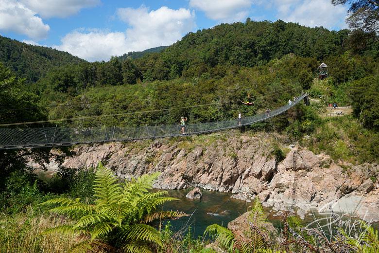 Simply Picture-New Zealand-Südinsel-Tasman-Buller Gorge Swing Bridge-Einige Personen auf der Hängebrücke über den Fluss