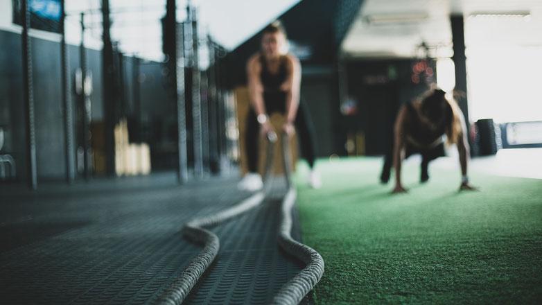 Zwei Frauen trainieren im Fitnessstudio. Die linke Frau trainiert mit den Seilen und die rechte Frau macht Liegestütze.