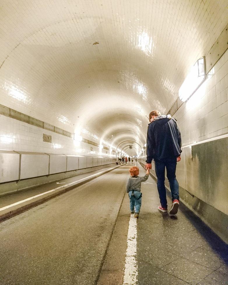 Kind geht an der Hand von Mann durch den alten Elbtunnel