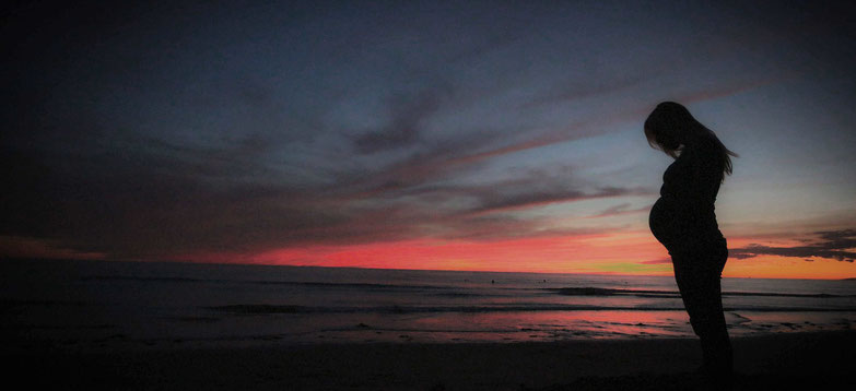 Donna incinta su una spiaggia al tramonto
