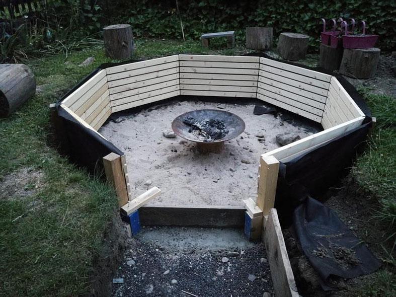 Im Boden vertiefte Garten-Feuerstelle mit Holzrostumrandung in 8-Eck-Format