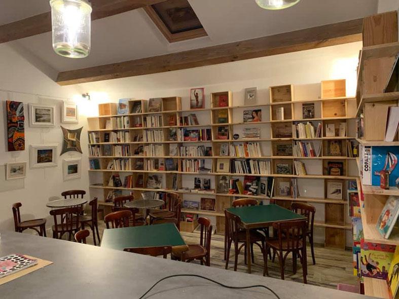 Librairie et tables se mêlent au sein d'un lieu chaleureux.
