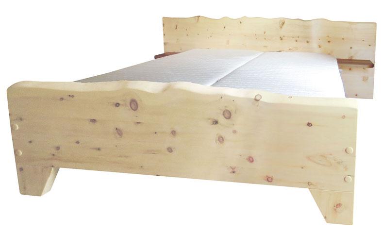 """Zirbenholzbett """"Freiheit"""", Kopfteil und Fußteil mit unregelmäßiger Baumkante, eitliche Ablagen aus Apfelholz am Kopfteil"""