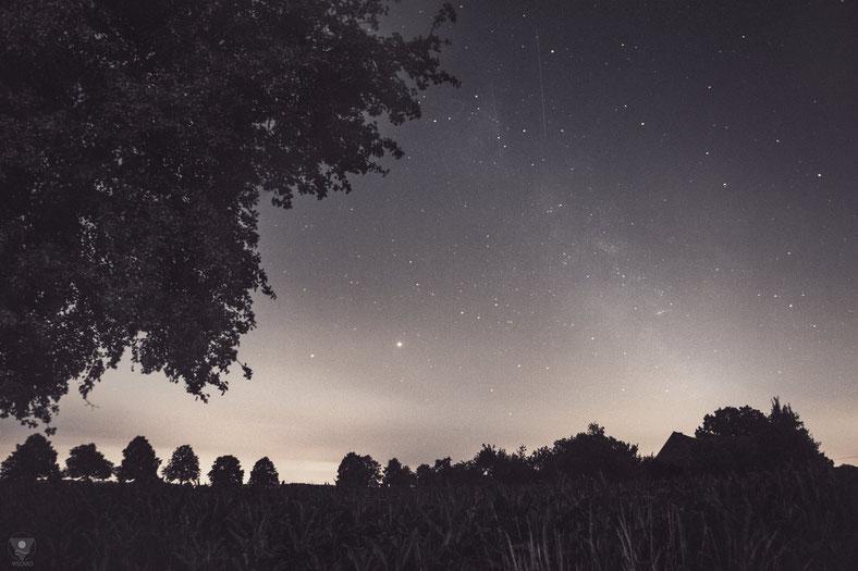 Saturn und Jupiter leuchten am Horizont nebeneinander. Oben im Bild fliegen mehrere Starlink-Satelliten durch die Nacht.  |www.visovio.de sternenhimmel, night sky, jupiter, saturn, starlink, weroamnordrheinwestfalen