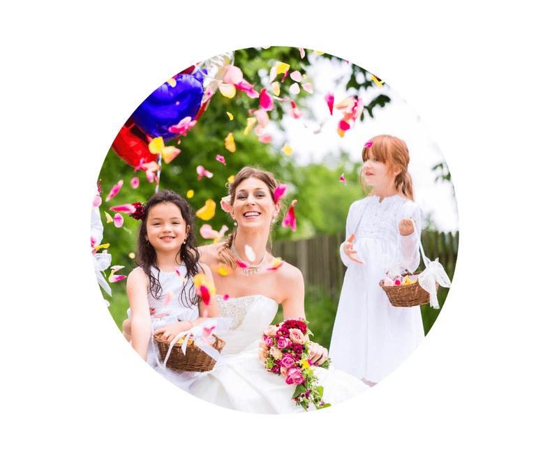 Blumenmädchen auf einer Hochzeit streuen Blumen über eine Braut