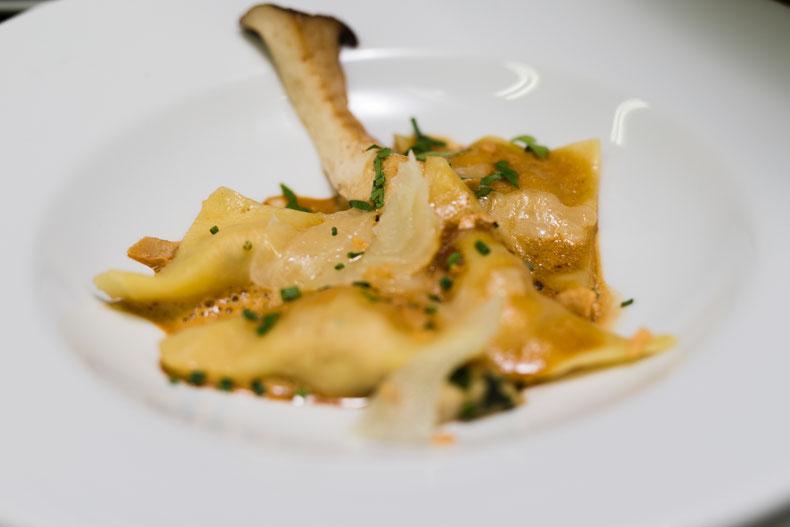 Hausgemachte Kaninchen-Ravioli mit gebratenen Kräuterseitlingen, geröstetem Knoblauch und Manchego