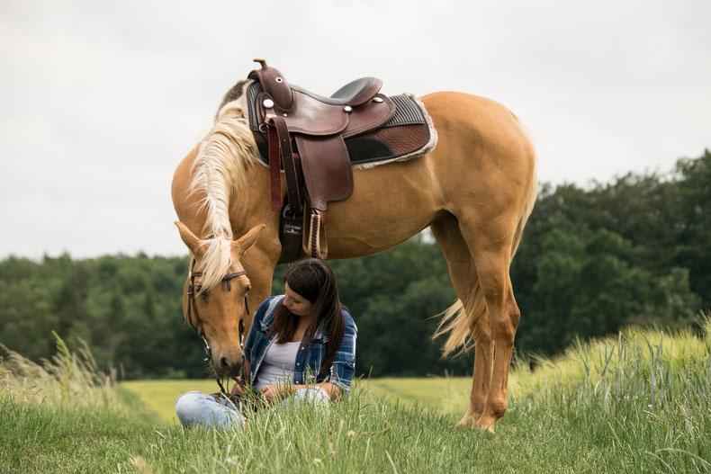 Frau sitzt vor Pferd im Gras