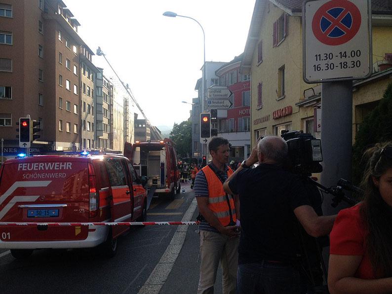 Interview mit TV-Team, im Hintergrund Grossbrand Olten mit Feuerwehr
