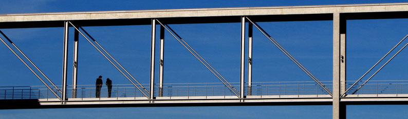 Zwei Menschen unterhalten sich auf einer Brücke, im Hintergrund blauer Himmel: Symbolbild für Kommunikation ist überall.