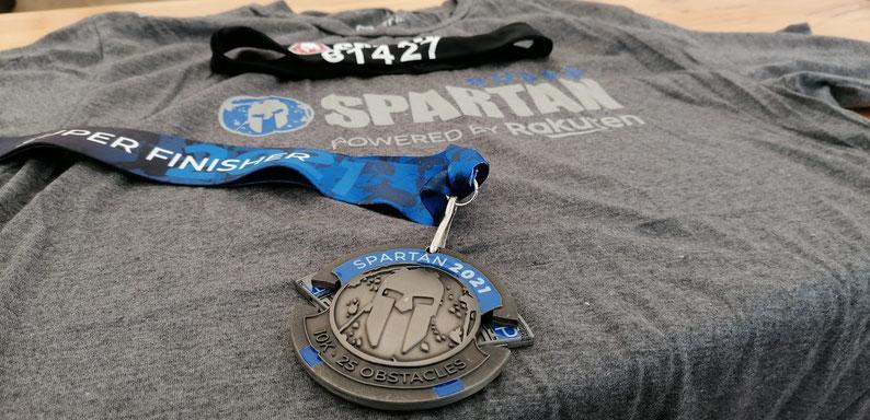 Wenn man es bis ins Ziel schafft, bekommt man ein T-Shirt sowie eine Medaille. Zusätzlich zur Gewissheit, sich selbst in den Allerwertesten getreten und eine echte sportliche Leistung erbracht zu haben.