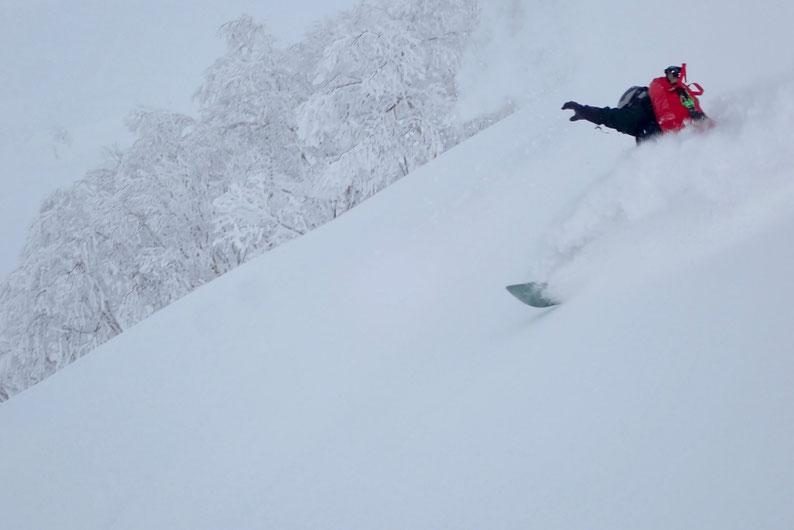 スプレーを巻き上げるスノーボーダー