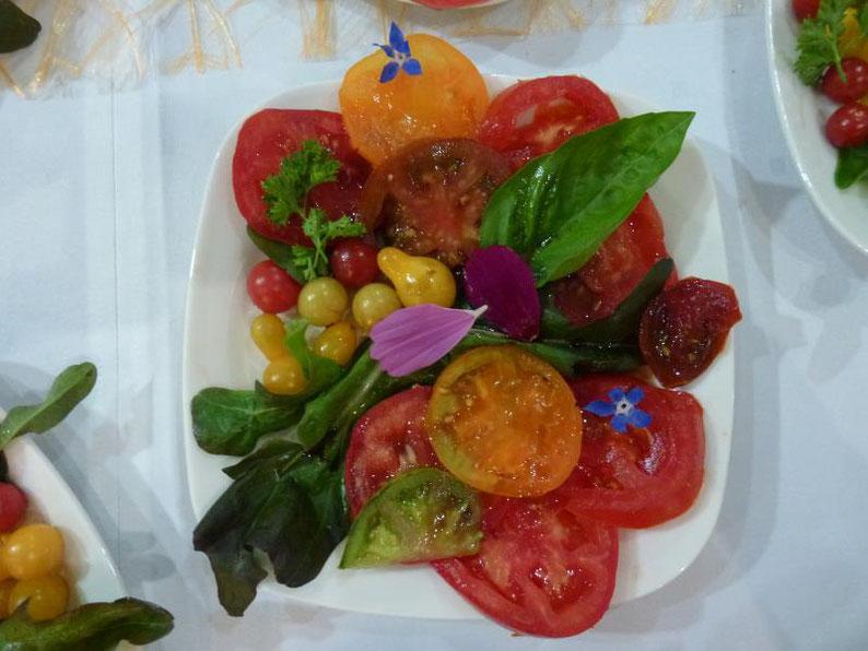 Tomates multicolores avec des fleurs de bourraches et des pétales de cosmos