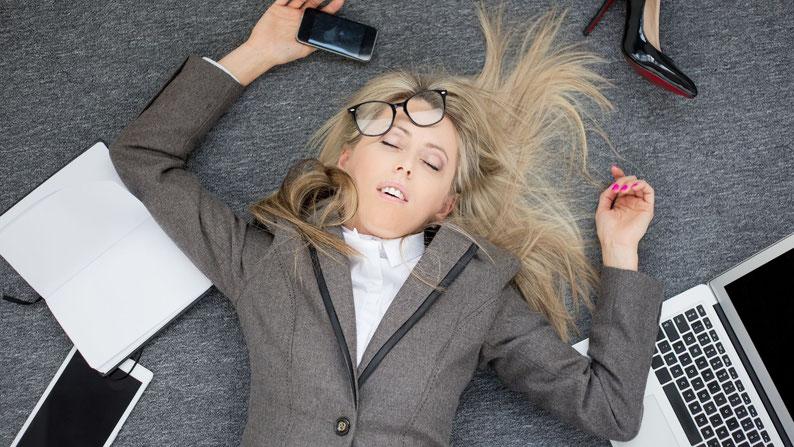 Jeune femme blonde en tailleur effondrée par terre, qui croule sous le travail. On y voit un agenda ouvert, un téléphone portable et un PC portable.