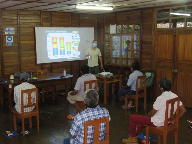 Un hombre con mascarilla está de pié presentando unos gráficos. Un grupo de cinco personas, sentadas manteniendo un metro de distancia entre sí, mira la presentación.