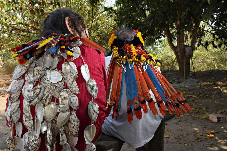 Duas mulheres Rikbaktsa sentadas de costas.  A da esquerda tem adorno de penas coloridas e o colar tutãra feito de conchas, preso no topo de suas costas. Foto: Adriano Gambarini/OPAN.