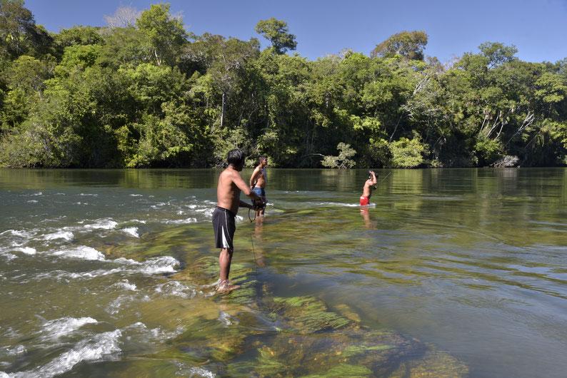 Início da pesca de mascreação no rio Cravari com floresta ao fundo, correnteza e águas transparentes, com macrófitas em pedras submersas. Indígenas do povo Manoki estão no meio do rio, e dois deles têm apetrechos de pesca subaquática na mão. Foto: Adriano