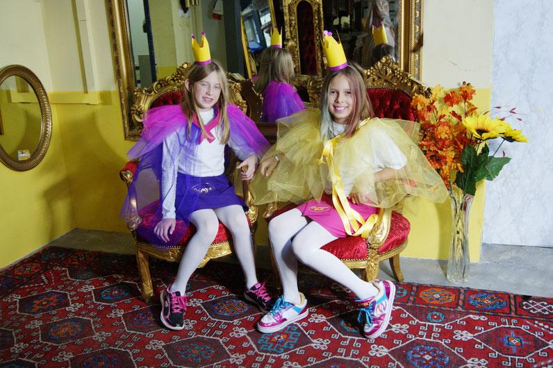 Elena und Elena, die Freundinnen, sitzen auf ihren Prinzessinnensessel und lachen in die Kamera.