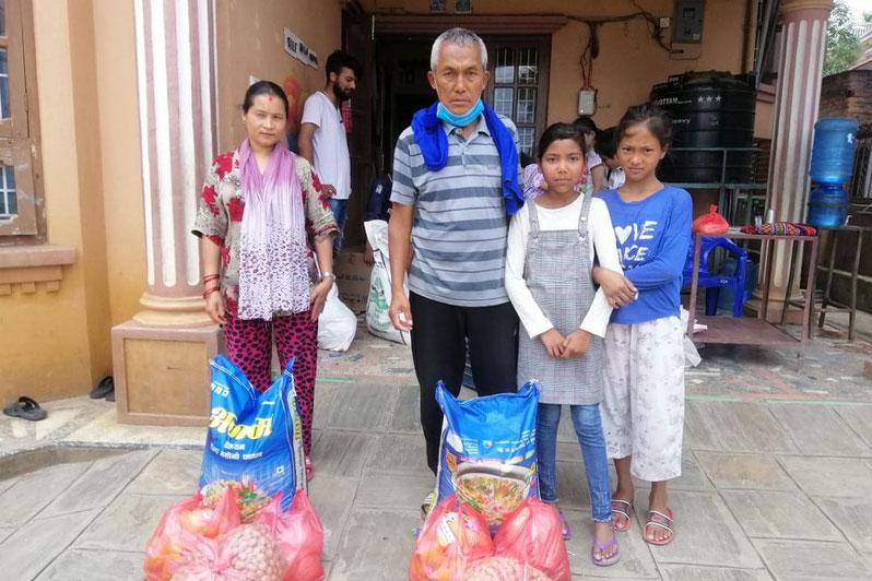 Familie mit Lebensmittelpaket in Kathmandu im Rahmen unserer Verteilaktion für vom Lockdown betroffene