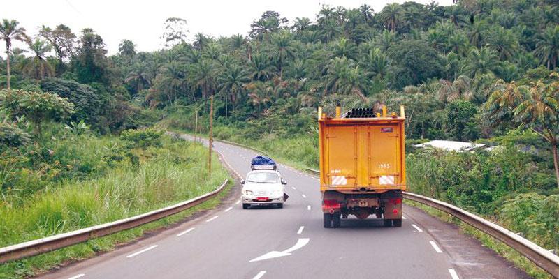 Un camion et un car de transport se croisent sur une route du Cameroun