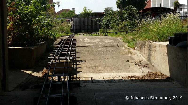 Gartenabhn 5 Zoll: Blick aus der Garage auf die Strecke. Die Rampe ist als Vierschienengleis mit den Spurweiten 5 Zoll (127 mm), 7 1/4 Zoll (184 mm) und 10 1/4 Zoll (260 mm) ausgeführt.