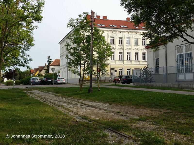 Straßenbahnlinie 360: Bahnhof Perchtolsdorf Brunnergasse, erhaltener Fahrleitungsmast und Weiche, Blick Richtung Mödling.