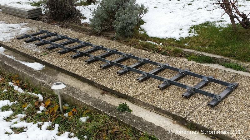 3 m langes Gleisjoch, Spurweite 260 mm. Die Schwellen bestehen aus einem U-Leichtprofil 50x25x3, die Schienen aus einem Rechteckprofil 35x12 (Werkstoff S355). Zum Vergleich: Der Weg ist 1 m breit.