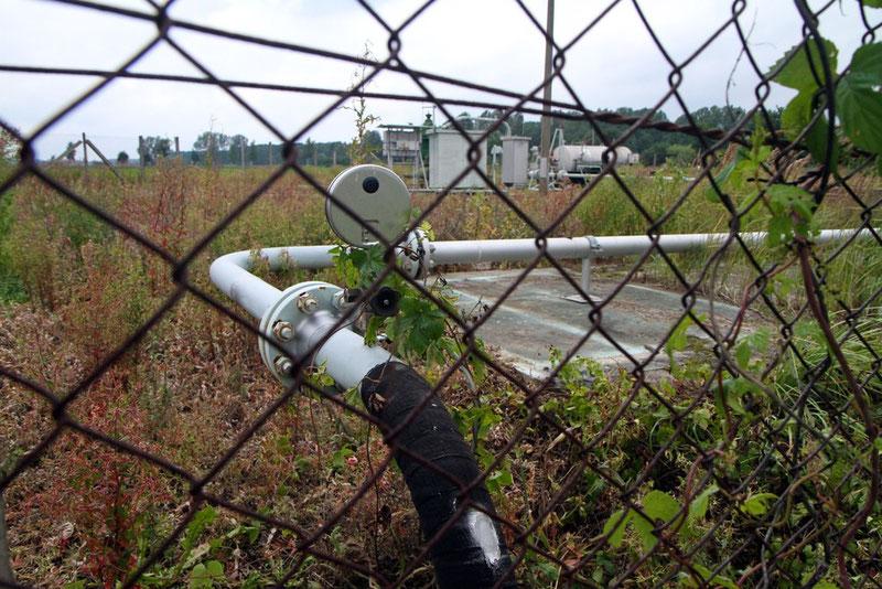 Das Bild zeigt eine noch aktive Erdgas-Fördersonde, deren Gasableitung (im Vordergrund, dient dem Transport des Rohgases zur Gassammelstelle) nahe am Begrenzungszaun steht.