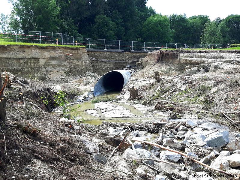 Durch Überströmen schwer beschädigter Straßendamm knapp vor der Einmündung des Antersdorfer Bachs in den Simbach. An dieser Stelle fanden bereits Aufräumarbeiten statt.