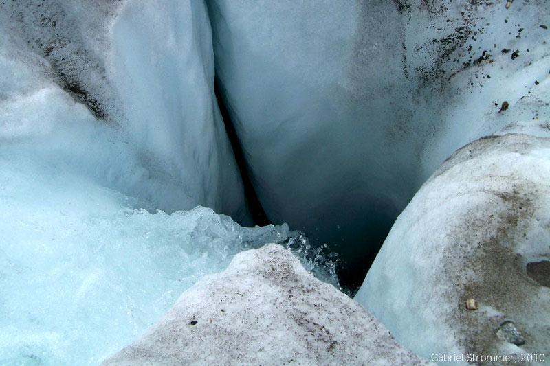 Schmelzwasserbach verschwindet in einer Gletschermühle