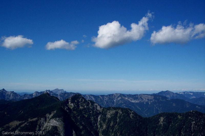"""""""Wolkenstraße"""" aus kleinen Haufenwolken (Cumulus humilis) über einer Gebirgskette"""