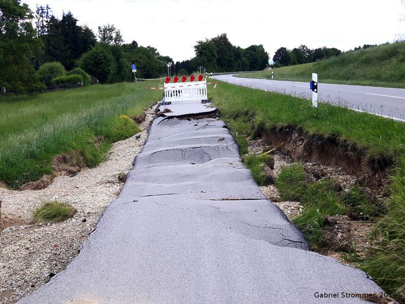 Durch Überströmen eines Straßendammes beschädigter Radweg entlang der St 2112