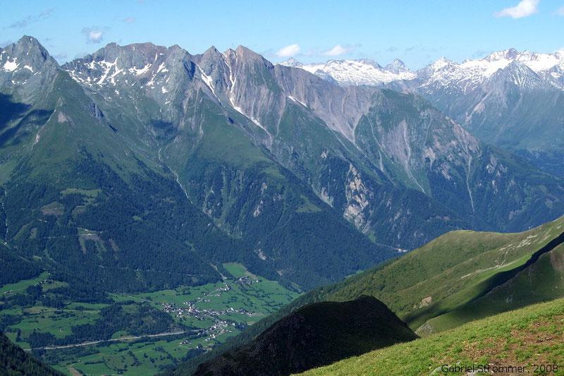 Die Virgener Nordkette (von links nach rechts: Mittereggspitze (3045 m), Göriacher Röte (3020 m) und Ochsenbug (3007 m)) vom Gipfel der Scheibe aus gesehen. Im Tal ist der Ort Obermauern zu erkennen, im rechten Bildhintergrund die Granatspitzgruppe